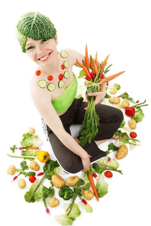веселая девушка держит овощи и фрукты