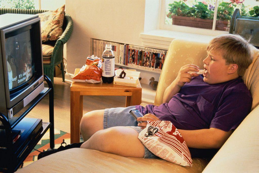 толстый мальчик смотрит телевизор
