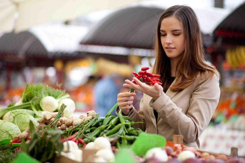 девушка покупает ранние овощи