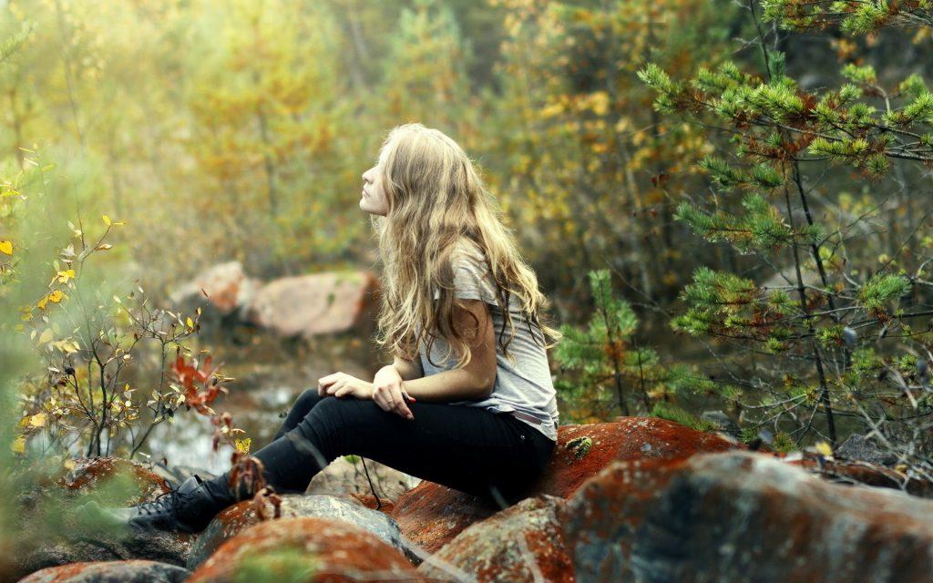 девушка сидит на камне в лесу