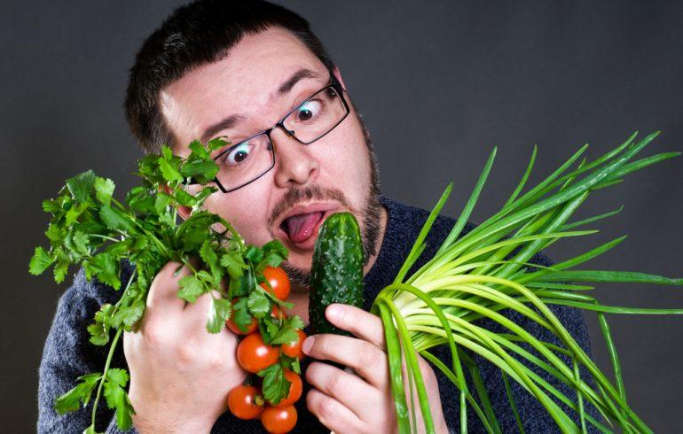 свежие овощи и фрукты кушает мужчина