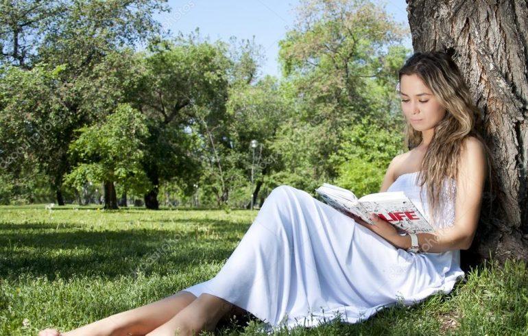 девушка читает книгу в парке