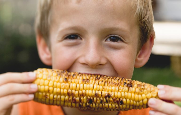ребенок кушает кукурузу