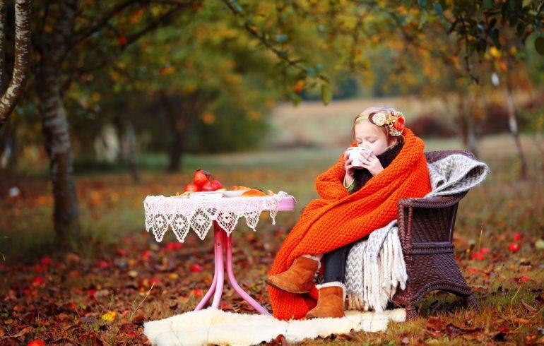девочка в пледе пьет чай