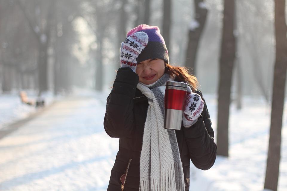 девушка гуляет зимой и пьет чай из термоса