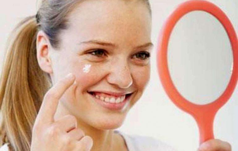 Девушка мажет зубной пастой черные точки на лице