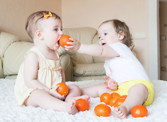 малыши играют с мандаринами
