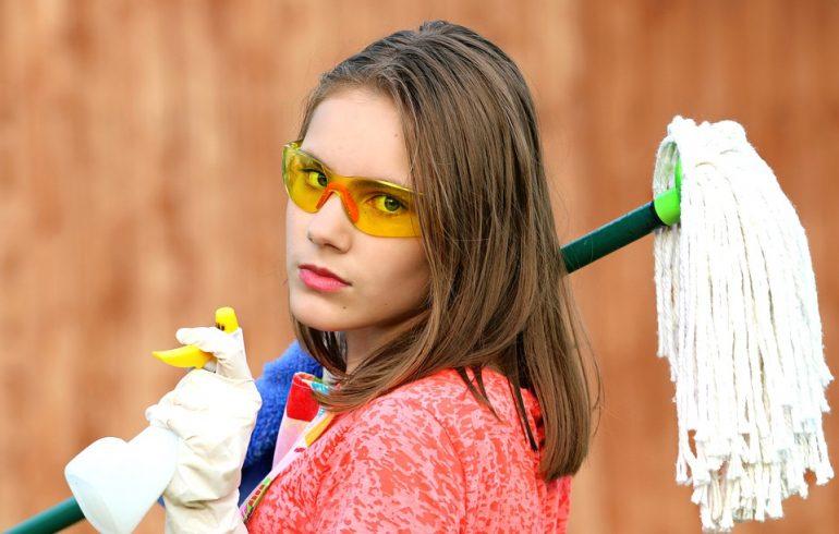 девушка в очках держит швабру