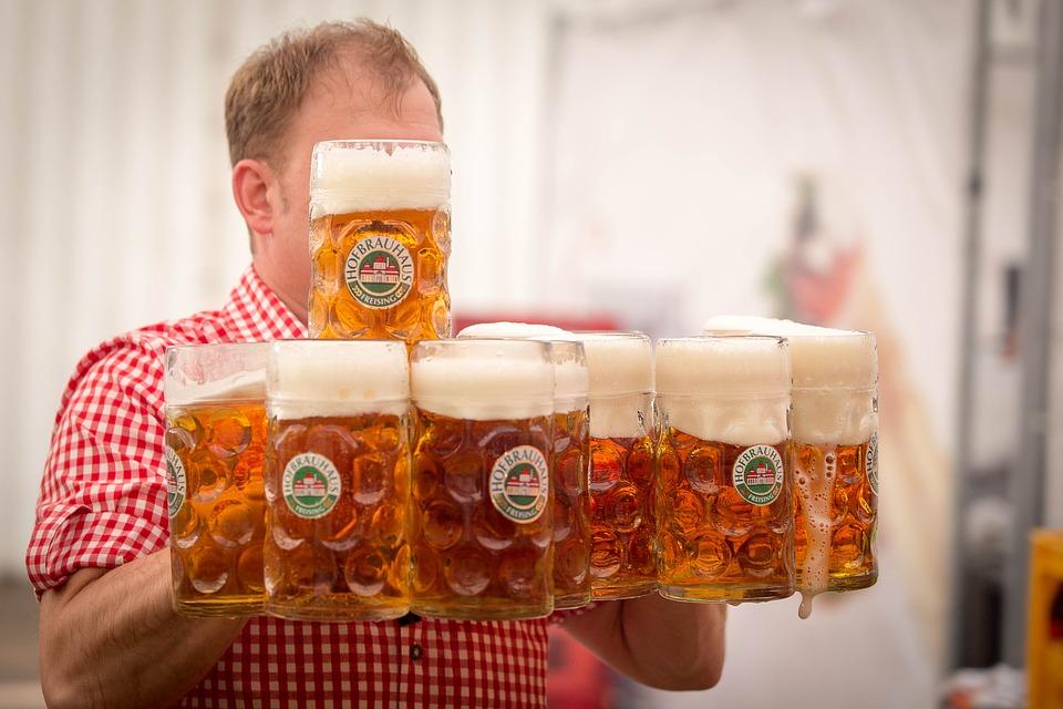 много кружек с пивом в руках у бармена