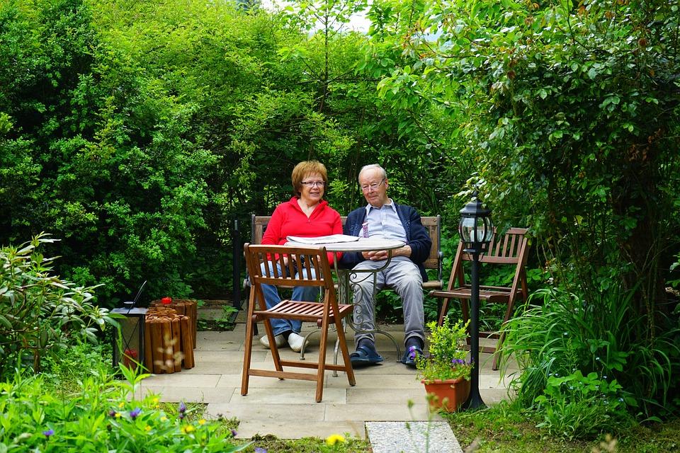 зрелая пара в зеленом уголке загородного дома