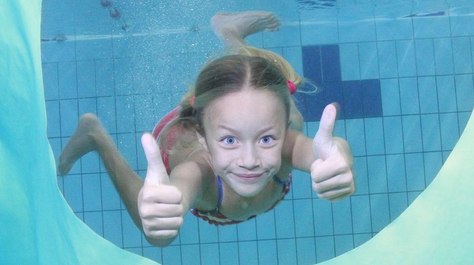 девочка ныряет в бассейне