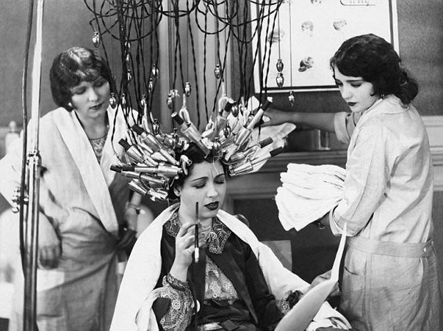 женщина делает завивку волос в салоне