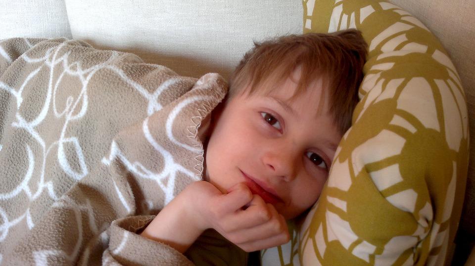 ребенок лежит на диване с подушкой