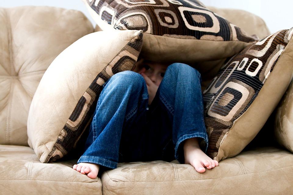 мальчик с подушками сидит на диване