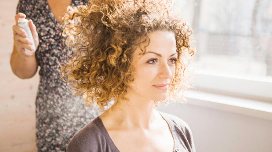 женщина с кудрявыми волосами делает прическу