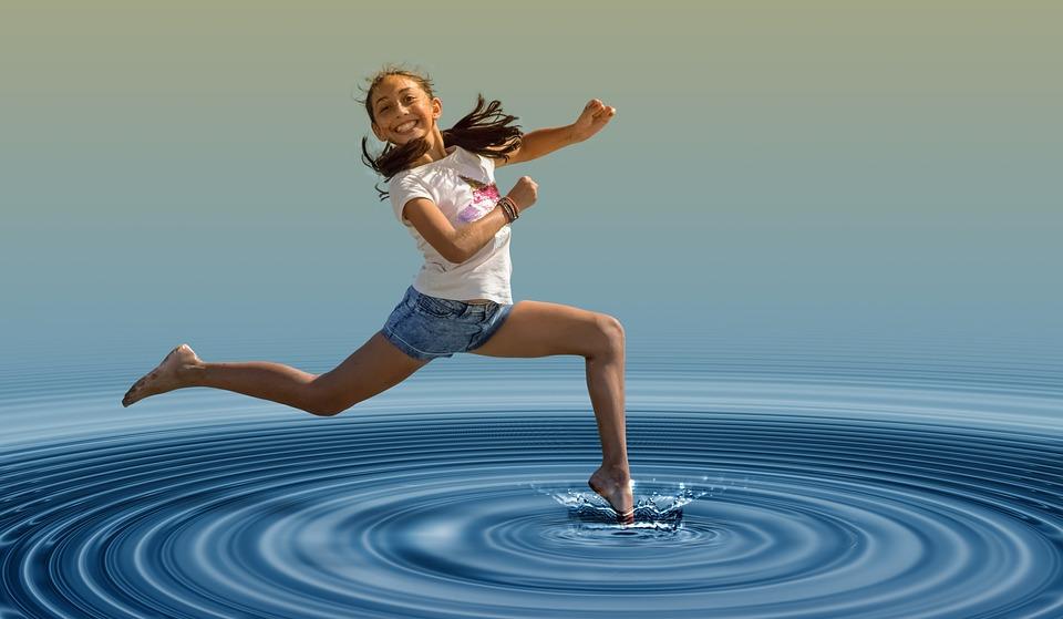 счастливая девочка прыгает по воде