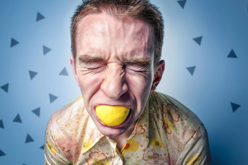 мужчина держит лимон во рту