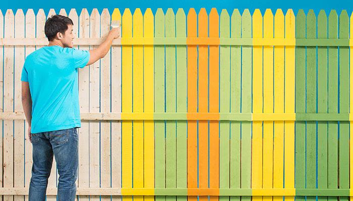 мужчина красит забор