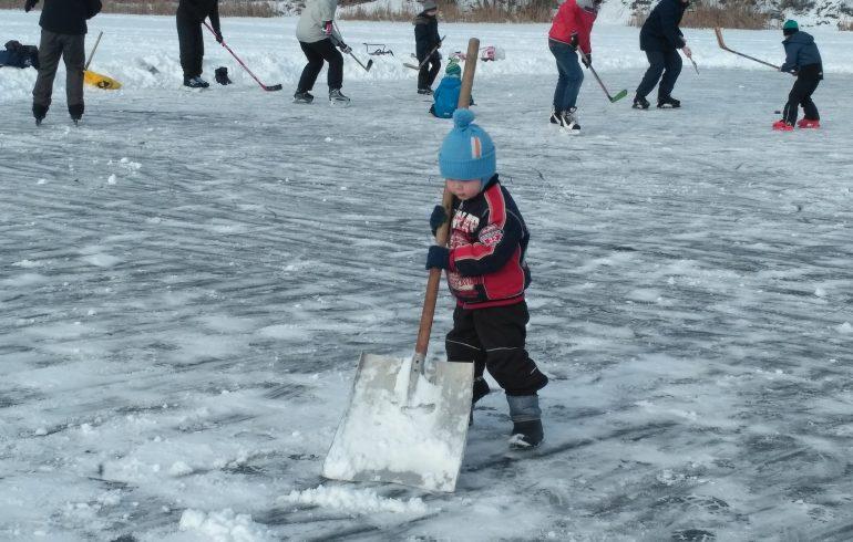 мальчик убирает снег для игры в хоккей