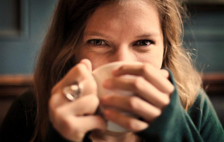 девушка вдыхает запах напитка из кружки