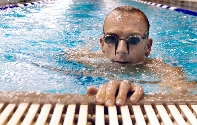 мужчина в бассейне в плавательных очках