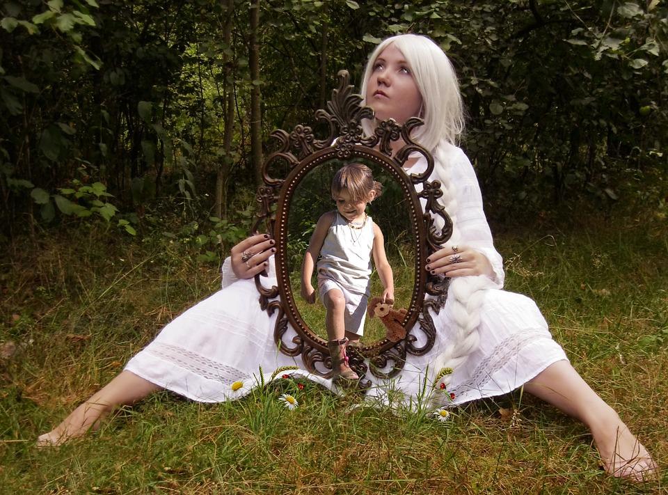 девочка в лесу держит зеркало