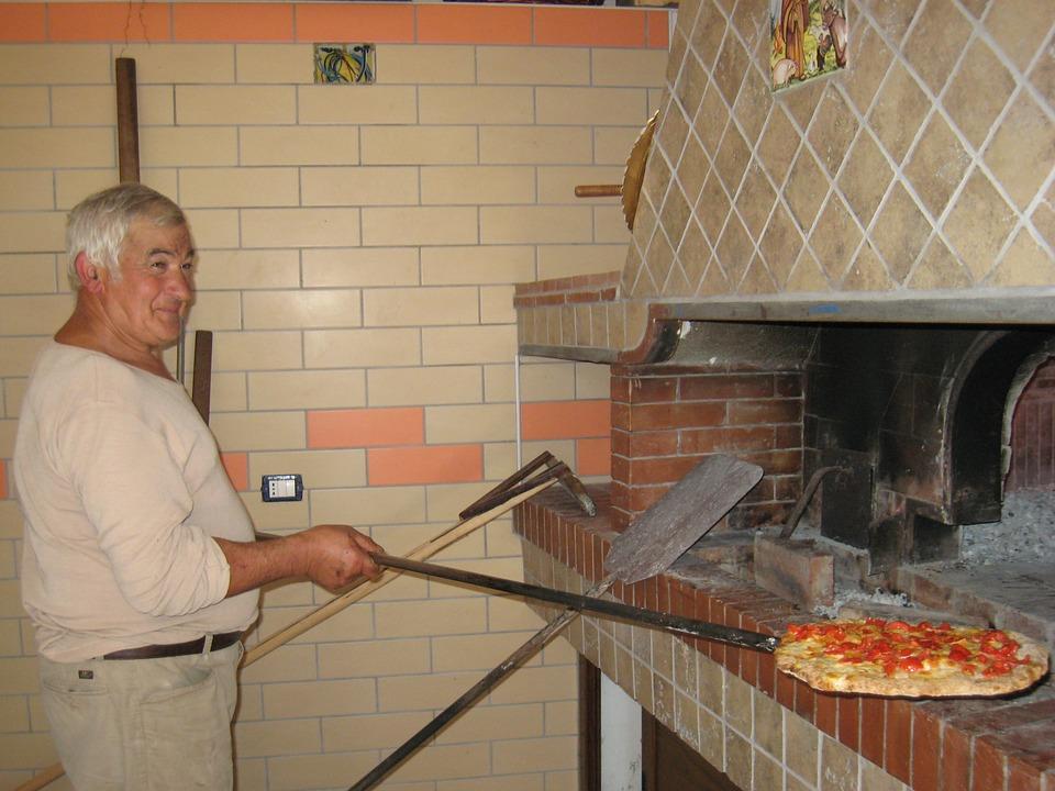 шеф повар готовит пиццу в печи