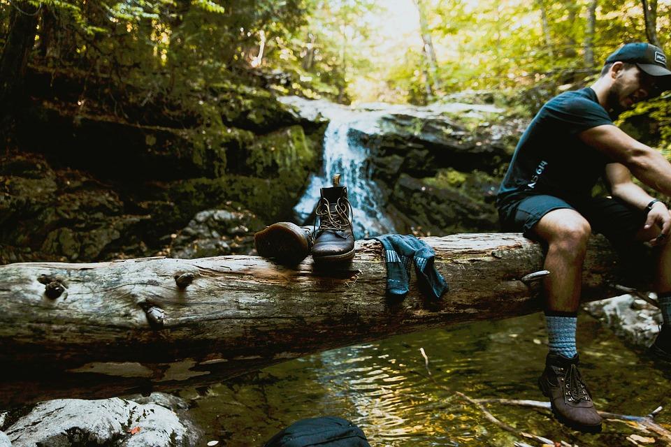 мужчина меняет обувь в походе у реки