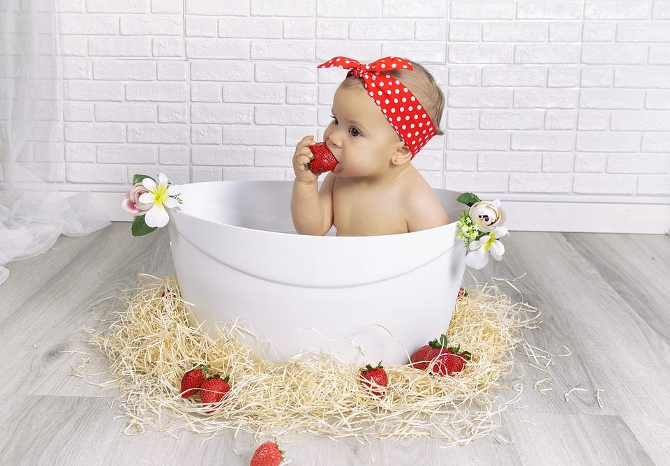 девочка в ванне пробует клубнику