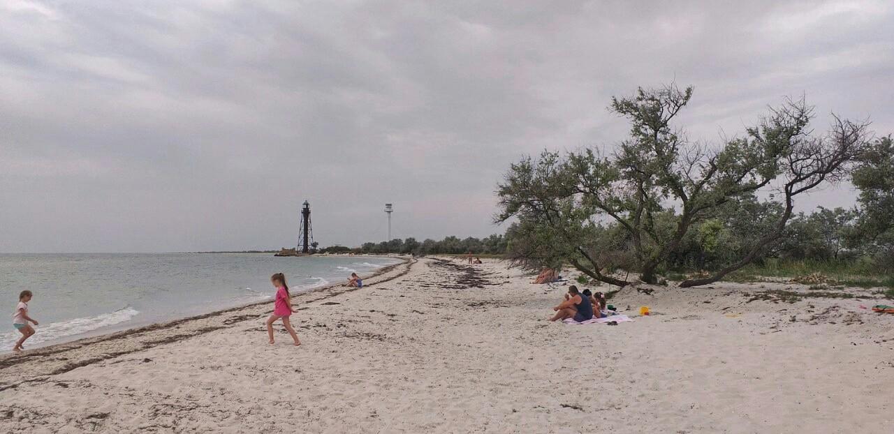 люди отдыхают на пляже Черного моря на острове Джарылгач