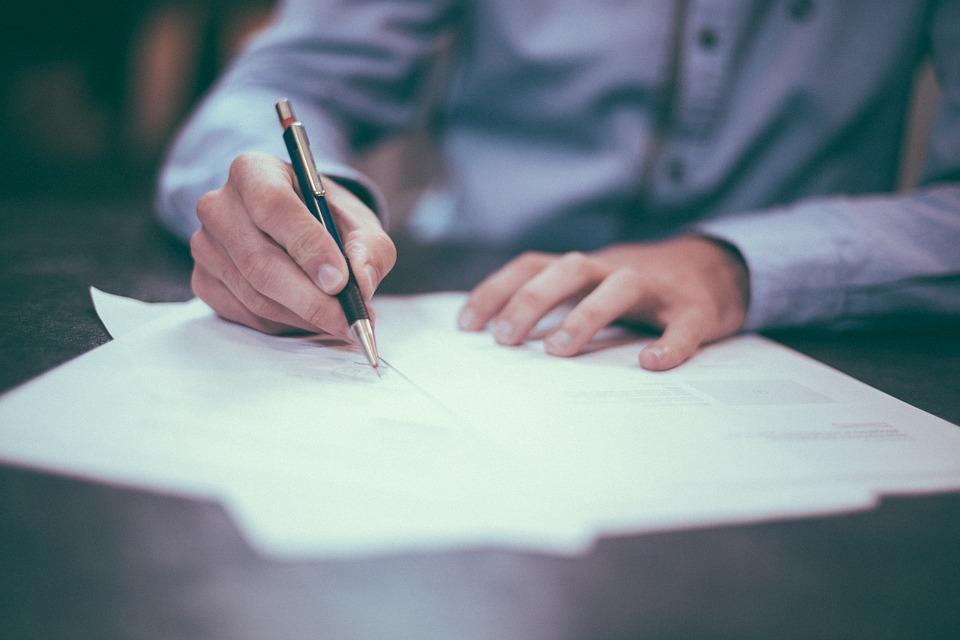 мужская рука держит ручку и пишет на бумаге