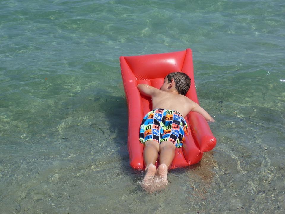 мальчик плавает в море на матрасе