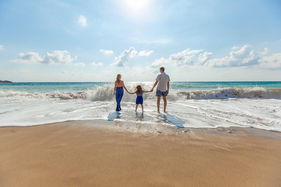 семья с малышом гуляет по берегу моря