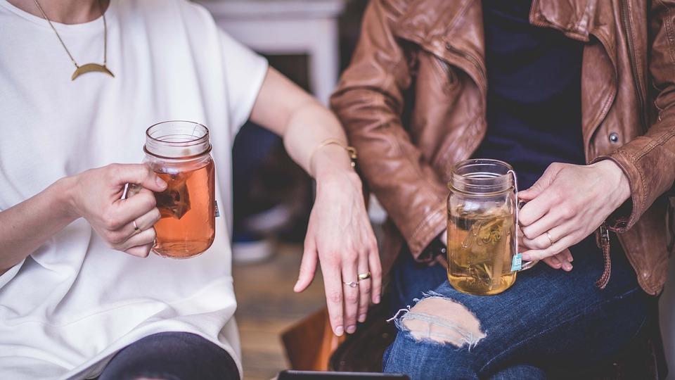 пара держит в руках кружки с чаем