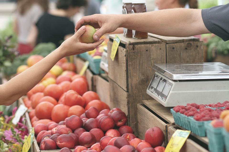 продавец яблок на рынке и покупатель