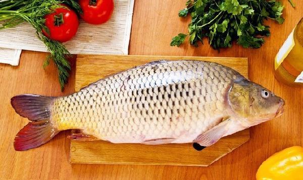 рыба карп на кухонном столе