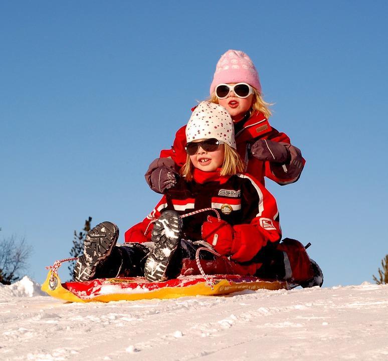 девочки катаются на санках зимой