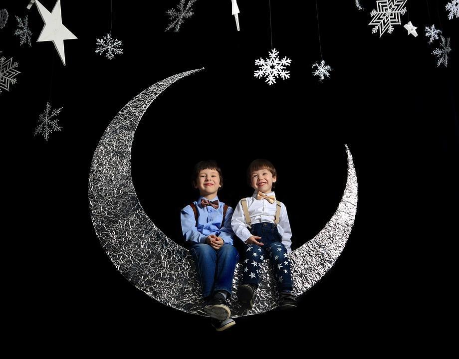 дети сидят на искусственном месяце в Новый год