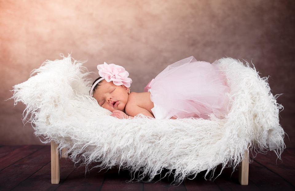 малышка в нарядном платье на кровати