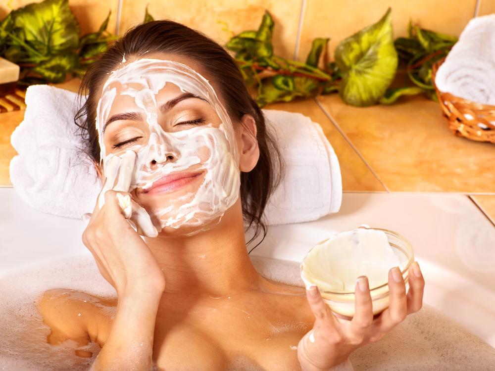 женщина наносит на лицо маску из сметаны и молока