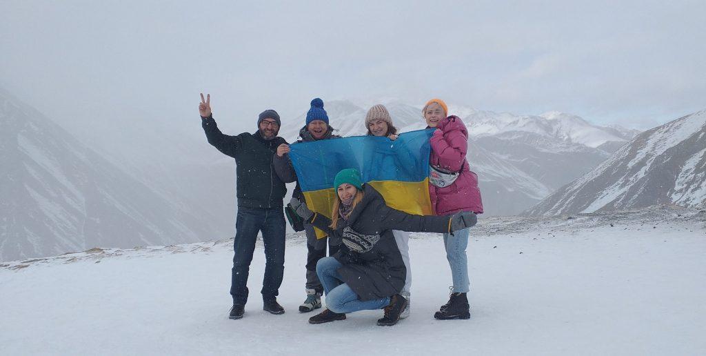 на вершине горы курорта Гудаури туристы с украинским флагом
