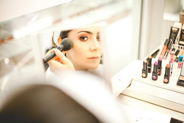 женщина делаем макияж у зеркала
