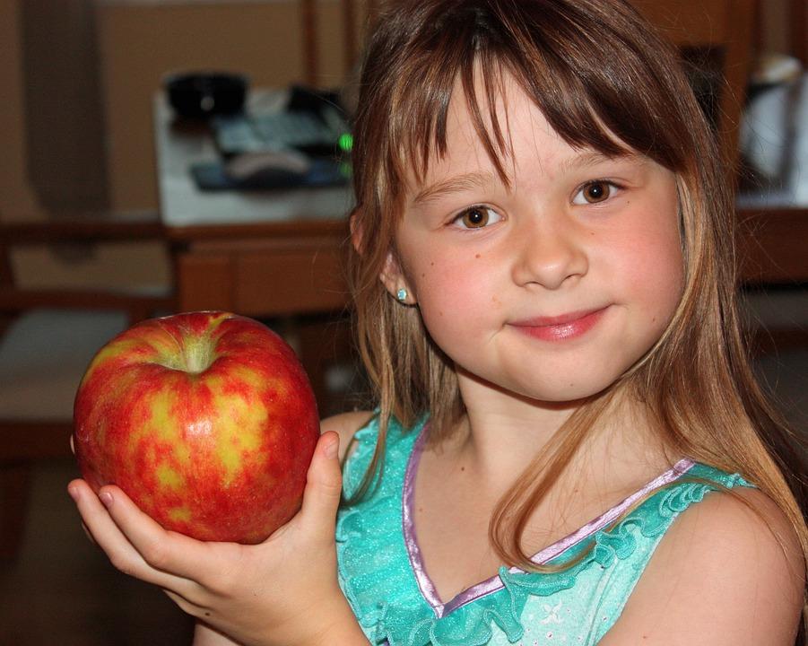девочка держит яблоко