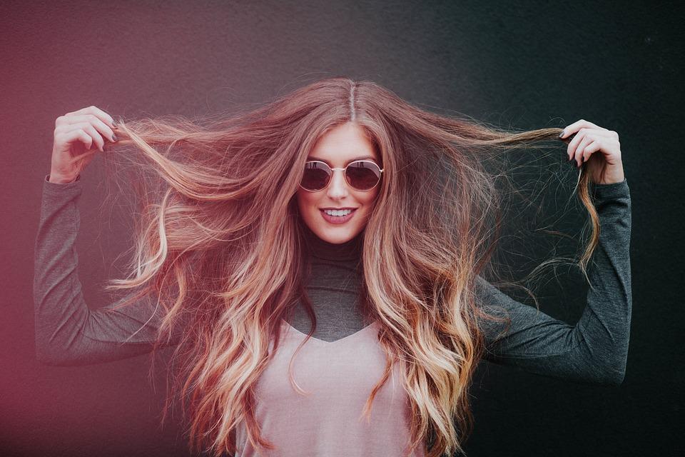 девушка в очках трогает волосы